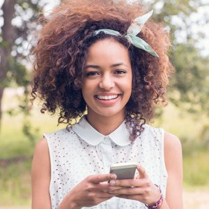 happy-young-woman-using-smartphone-on-a-sunny-day-P8PX76C.jpg